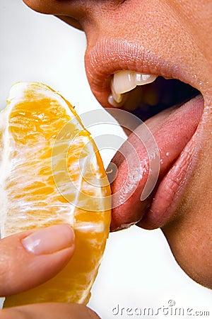 Pretty woman licking orange slice