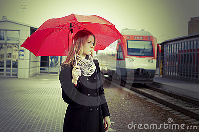 Pretty woman near the train travelling in station