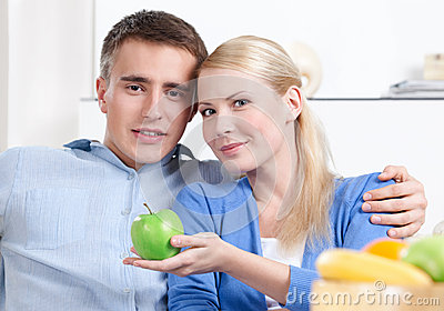 Pretty woman offers an apple to her husband