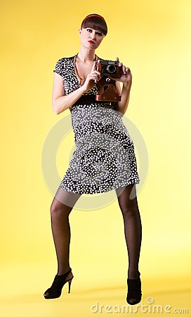 Pretty woman with old-style photo camera