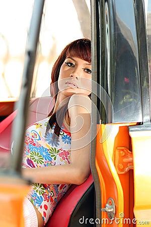 Pretty woman in orange car