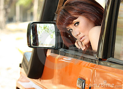 Pretty woman in orange car