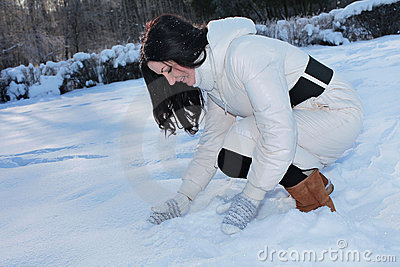 Pretty woman playing with snow