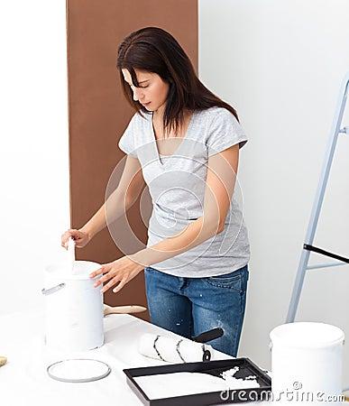 Pretty woman preparing white paint to renovate
