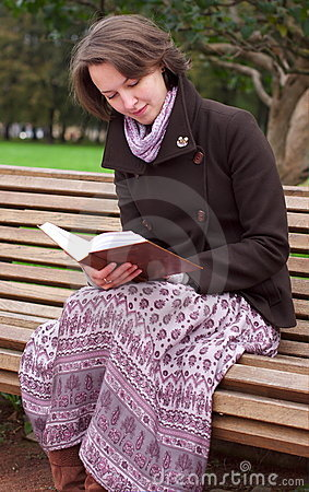 Pretty woman reading a book on a bench