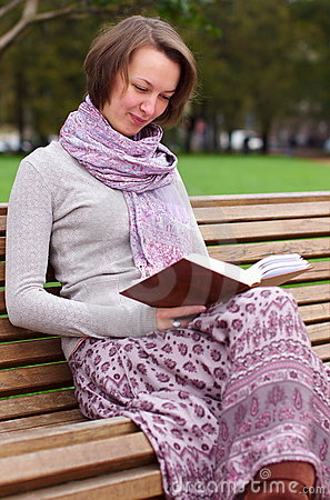 Pretty woman reading a book on a bench and smiling