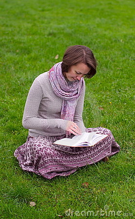 Pretty woman reading a book on a grass