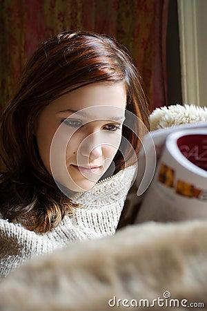 Pretty woman reading magazine