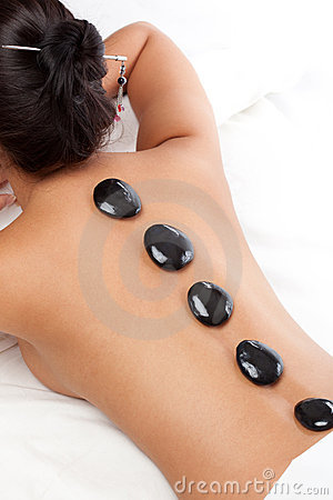 Pretty woman receiving a therapy with hot stones