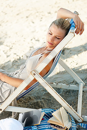 Pretty woman relaxing on a deck chair by the beach