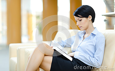 Pretty woman rests at the sofa with book
