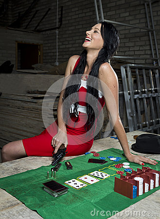 Pretty woman with revolver laughing at poker table