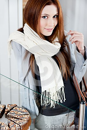Pretty woman in scarf looking at the bakery window