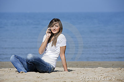 Pretty woman sit down on the sand with cellphone