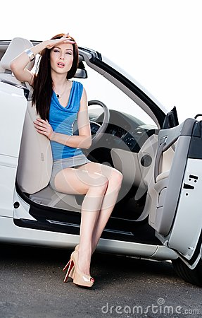 Pretty woman sits in the car with door opened