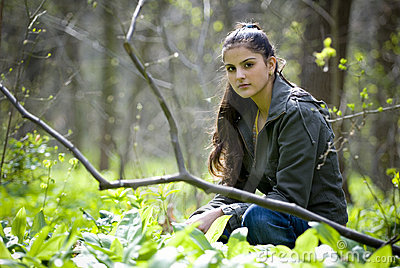 Pretty woman sitting in forest