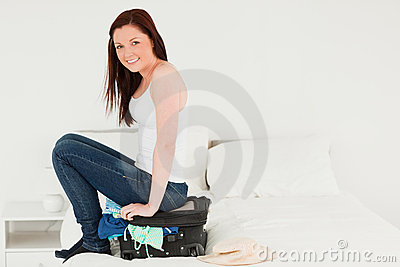 Pretty woman sitting on her suitcase