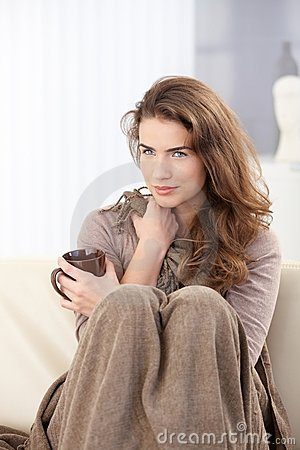 Pretty woman sitting on sofa drinking tea