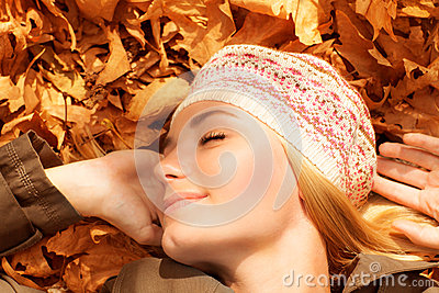 Pretty woman sleeping on fall foliage
