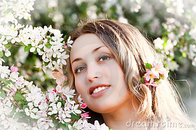 Pretty woman among a spring blossom