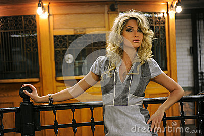 Pretty woman standing by old token booth