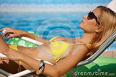 Pretty woman sunbathing by pool