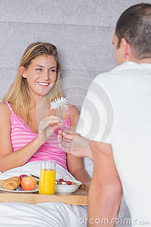 Pretty woman taking a daisy from partner at breakfast in bed