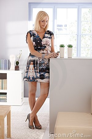 Pretty woman texting on mobile at home