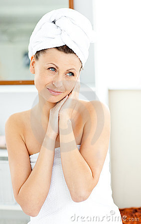 Pretty woman with towel putting cream on her face