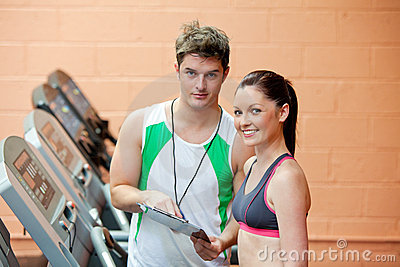Pretty woman on a treadmill with her coach