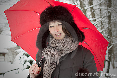 Pretty woman with umbrella look in winter snow