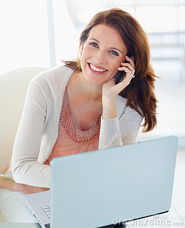 Pretty woman using cellphone with laptop in front