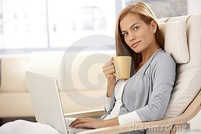 Pretty woman using laptop having tea