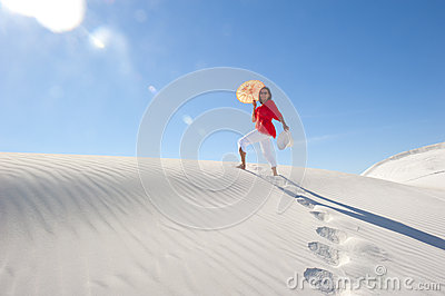 Pretty woman walking up sand dune in summer heat