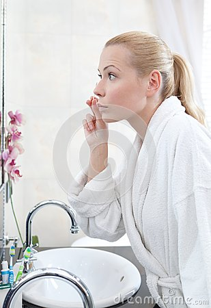 Pretty woman washes face with lotion