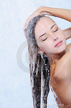 Pretty woman washing her hair in a shower