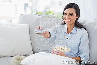 Pretty woman watching tv eating popcorn