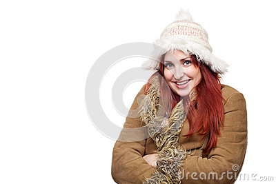 Pretty young woman wearing winter coat and furry hat, smiling and