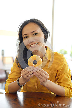 Free Pretty Young Attractive Woman Eating Donut  At Caf Stock Photo - 44069770