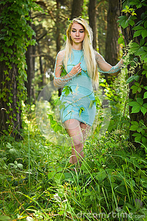 Free Pretty Young Blonde Girl With Closed Eyes And Long Hair In Turquoise Dress Standing In The Green Forest Where Trees Are Enlaced Wi Royalty Free Stock Photo - 87885745
