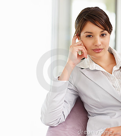 Pretty young business woman sitting on a chair