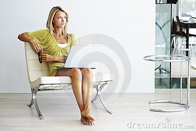 Pretty young female with laptop looking away
