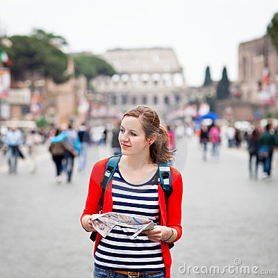 Pretty young female tourist holding a map
