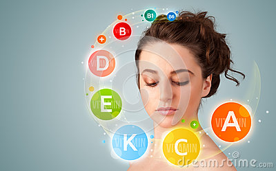 Pretty young girl with colorful vitamin icons and symbols Stock Photo