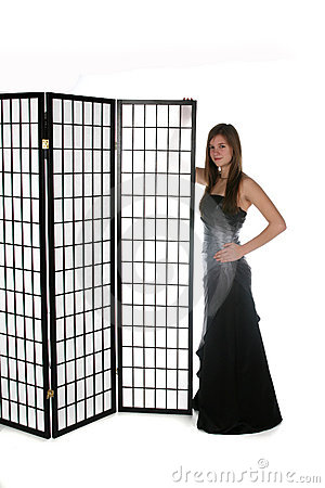 Pretty young girl in formal gown next to screen