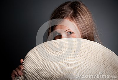 Pretty young girl is hiding behind the hat