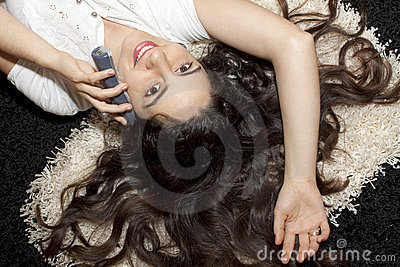 Pretty young girl lying on carpet with telephone