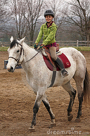 Cute Young Girl Riding Horse On A Spring Day