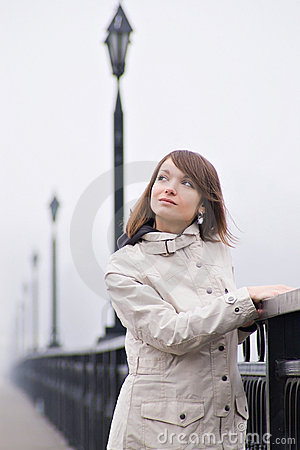Pretty young girl in white coat on a bridge