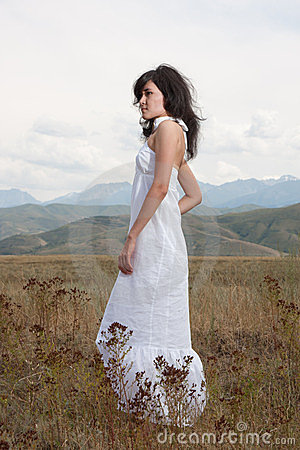 Pretty young lady on a meadow hills
